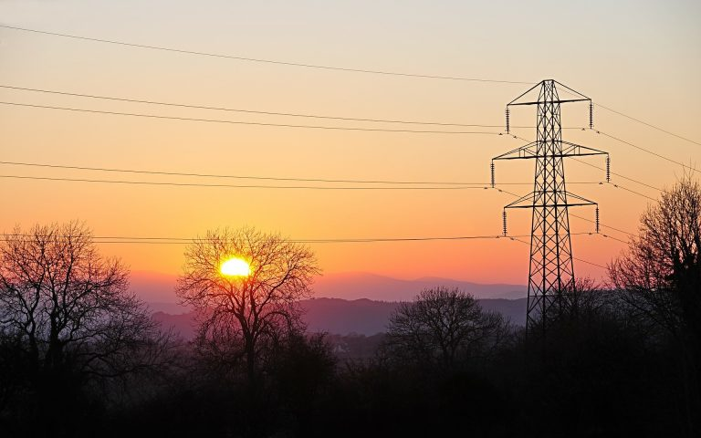 powerlines and cables shown with setting sun behind
